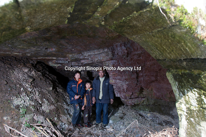 Retird in 1997, Yang Tongzai, 67, a former mercury miner in the hole #6 since 1966, poses for pictures inside a mine opening with his 2 grandsons in Man Shan Special Region in Guizhou. Yang lives on his monthly retire pension 960RMB with his family of 6, he got both pneumoconiosis & mercury poisoning diseases (bad teeth) in the early 80s.