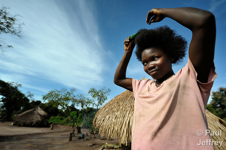 Crematina Mikowma, 16, combs her hair in the Makpandu refugee camp, a ramshackle collection of huts with mud walls and thatched roofs spread through a remote section of forest 40 kilometers from Yambio, the capital of Western Equatoria State in the newly independent South Sudan. More than 3,000 people live in the camp, having fled the Democratic Republic of the Congo in 2008 when the Lord's Resistance Army started a murderous rampage through the area. In recent months the Congolese have been experiencing harassment and insults from the local population. Religious workers say the refugees want to go home to the Congo, but not until Joseph Kony and the LRA are removed.