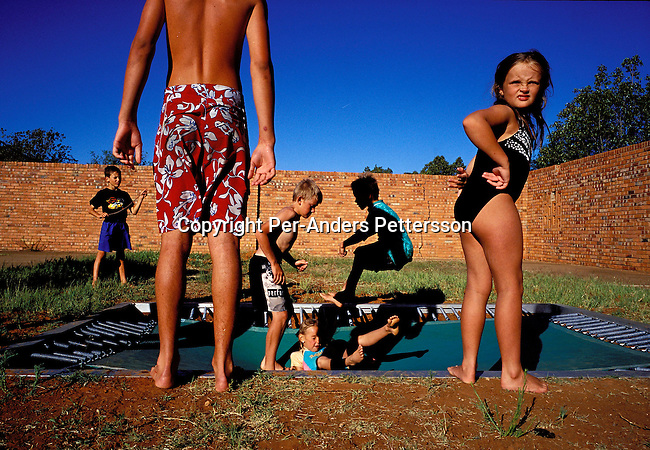dipplei00083 .People Leisure ORANIA, SOUTH AFRICA - Unidentified children play on a trampoline at a playground in Orania, on December 13, 2003 in Orania, in the Northern Cape Province, South Africa. The village was founded in 1991 and bought by descendants of Hendrik Verwoerd, the architect of Apartheid. ItÕs run as a private town only accepting whites. About 600 Afrikaners lives in the village where they celebrate their culture and keep traditions alive. They have chosen not to live in todayÕs South Africa; a country ran by a black government since 1994..©Per-Anders Pettersson/iAfrika Photos