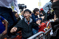 HONG KONG, CHINA - NOVEMBER 18: Students leader and Scholarism founder Joshua Wong Chi-fung stands on a barricade repositioned  by pro-democracy Occupy Central protesters on Lung Wui Road in font of Citic tower, on November 18, 2014, in Hong Kong, China. After a discussion the protesters and bailiffs came to an agreement, protesters moving the barricade away from the clearance zone defined by a court order, and bailiffs agreeing to let it stand there. Bailiffs successfully cleared a section of the Umbrella Revolution camp as protesters put up little resistance to the enactment of a court order to remove barricades blocking access to Citic Tower. (Photo by Lucas Schifres/Getty Images)