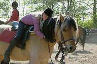 Mädchen beim Reitunterricht auf Ponyhof, Mädchen liebkost ihr Reitpony, Reiten, Reiterhof, Gestüt