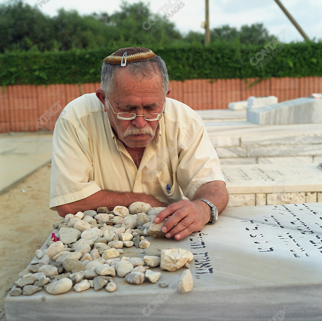Shlomo Yulis stands at the grave of his son, Rafael Yulis, who died of Lukimia at the age of 14 yrs.  He says that when he laid his son to rest he never imagined that he would have to uproot his grave. Gush Katif, Gaza, July 2005.