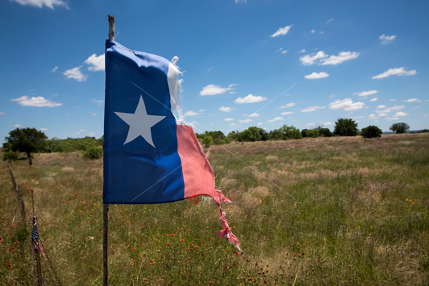 Worn and tattered State of Texas Flag flying in the gentle breezes of the Texas hill country.