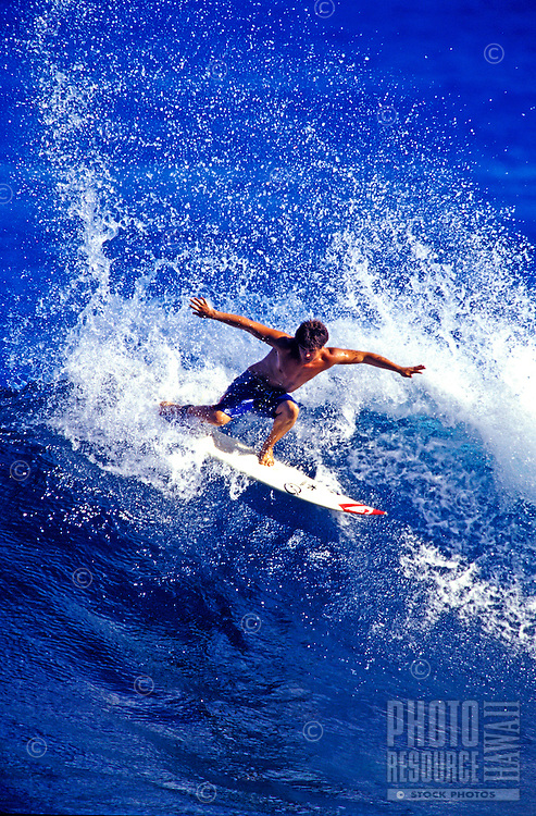 Surfer Benel Eleogram keeps his balance iamid the swirling whitewater of a breaking wave.