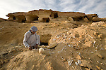 A local Siwan young man holds human remains found on the outskirts of the Siwa Town in the Siwa Oasis, Egypt near an abandoned and raided burial tomb.