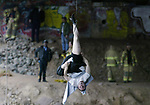 -A man hangs upside down from the bottom of the RT 18 South bridge over the Weston Mill Pond in New Brunswick as police & firefighters find a way to get to the man hanging by a rope attached to his leg. A fare in a passing cab  saw the man hanging from the bridge about 9:00 am on Sunday APril 11,2004 as the cab driver alerted New Brunswick Police. Police are investing cirumstances on how the man came to be under the bridge in the first place. (HOME NEWS TRIBUNE/MARK R. SULLIVAN CHIEF PHOTOGRAPHER)