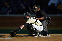 Wake Forest Demon Deacons catcher Shane Muntz (11) reaches for a low pitch as home plate umpire Gregory Street looks on during the game against the Liberty Flames at David F. Couch Ballpark on April 25, 2018 in  Winston-Salem, North Carolina.  The Demon Deacons defeated the Flames 8-7.  (Brian Westerholt/Four Seam Images)