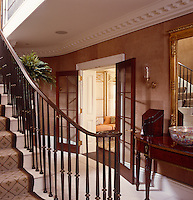 A staircase curves down to the elegant hall outside the dining room