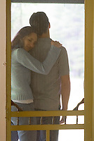 Man & woman embracing outside screen door