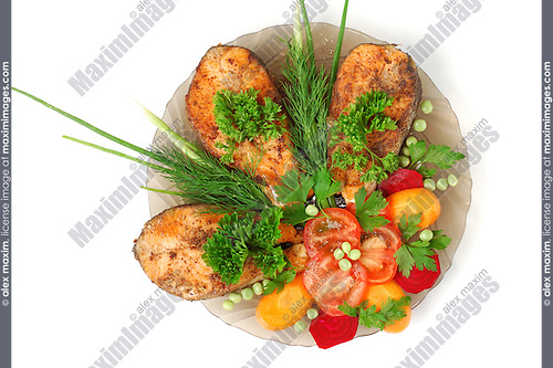 Baked salmon with vegetables on a plate isolated on white background