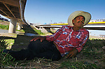Jose Bustamente rests under the bridge on the bank of the Rio Grande River in Matamoros. Bustamente was letting his cattle roam and feed on the banks.