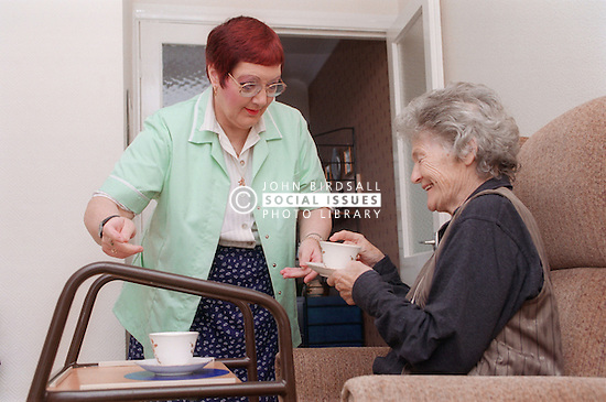 Carer giving elderly woman cup of tea,