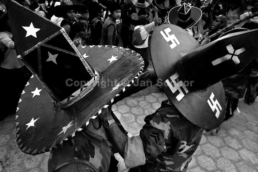 Indians, wearing cardboard hats with swastika symbol, dance during the Inti Raymi (San Juan) festivities in Cotacachi, Ecuador, 24 June 2010. 'La toma de la Plaza' (Taking of the square) is an ancient ritual kept by Andean indigenous communities. From the early morning of the feast day, various groups of San Juan dancers from remote mountain villages dance in a slow trot towards the main square of Cotacachi. Reaching the plaza, Indians start to dance around. They pound in synchronized dance rhythm, shout loudly, whistle and wave whips, showing the strength and aggression. Dancers from either the upper communities (El Topo) or the lower communities (La Calera), joined in respective coalitions, seek to conquer and dominate the square and do not let their rivals enter. If not moderated by the police in time, the high tension between groups always ends up in violent clashes.