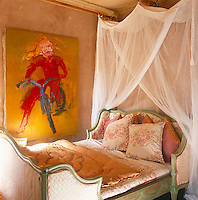 The French bed in this guest bedroom contrasts with a painting by Tonio Trzebinski of his daughter learning to ride