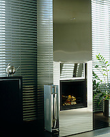The vertical design of a stunning contemporary stainless steel fireplace in the living room of a Helsinki apartment is accentuated by a pair of long Venetian blinds on either side
