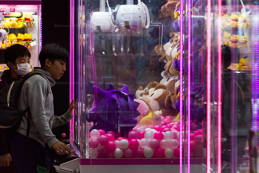 Two young Japanese boys play with a claw-catcher machine in a gaming arcade in Shinjuku, Tokyo, Japan. Friday March 22nd 2019