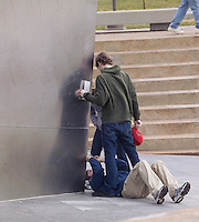 A Bloke flat on his back taking a photo looking upwards at his friends with the Saint Louis Gateway Arch in his photos background.
