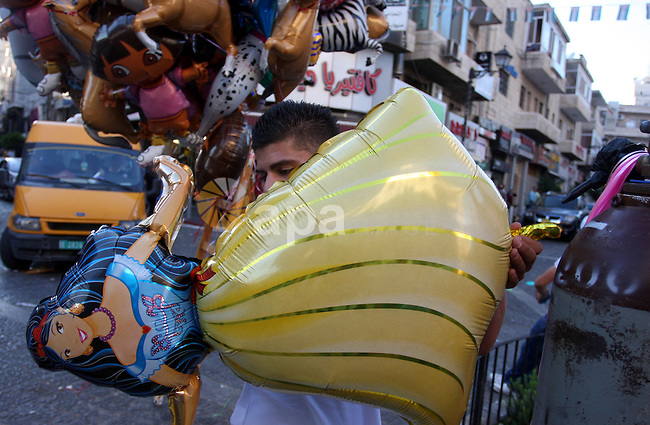 A Palestinian vendor sells ballons in the market during preparations for the Eid Al-Fitr feast in the West Bank city of Ramallah, on Aug 16, 2012, as Muslims over the world prepare to celebrate Eid al-Fitr, a three day holiday marking the end of the religious month of Ramadan in which believers abstain from food and water during daylight hours. Photo by Issam Rimawi