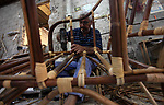 A Palestinian man works on bamboo furniture at workshop in Gaza city on June 13, 2019. Bamboo has a long history of use in furniture. Bamboo is a product of southeast Asian countries and before the Israeli blockade of the Gaza Strip, Gaza traders used to bring it in to the coastal territory in adequate quantities to allow the industry to remain viable. Photo by Mahmoud Ajjour