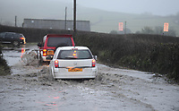 Vehicles make their way through flood water on the North Gower Road near Oldwalls, Gower, as heavy rained caused difficult driving conditions across Wales.