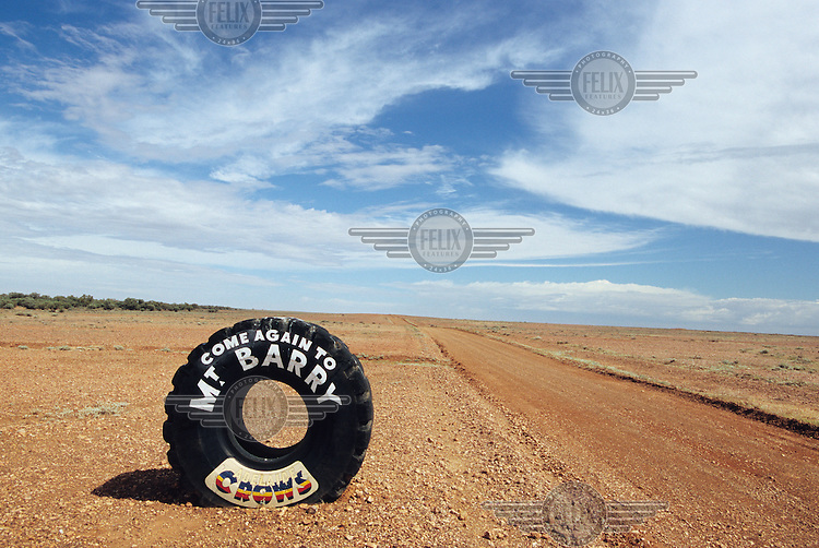 A painted tyre stands on the roadside at the exit from a farm in the outback...