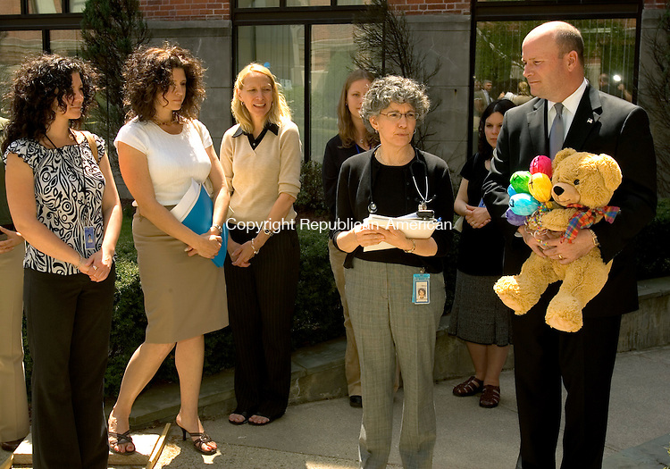 WATERBURY, CT- 24 APRIL 2008 --042408JS01-Joseph A. Geary, right representating the Mayor's office, holds a teddy bear presented to  Dr. Sandra Carbonari, second from right, as she talks about the importance of immunizations during a health fair Thursday at the Waterbury Deaptment of Public Health. Dr Carbonari, a Pediatrician at the Childrens Health Center at Saint Mary's Hospital in Waterbury and the staff, were recently honored by the state legislature as an immunization champion.<br /> Jim Shannon / Republican-American