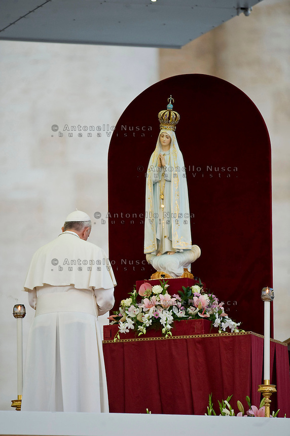 Papa Francesco in preghiera davanti la statua della Madonna di Fatima. Pope Francis places a rosary at the foot of a statue of Our Lady of Fatima in St. Peter's square before leadng a prayer as part of a Marian Day event at the Vatican.