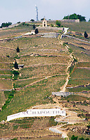 The Hermitage chapel, a sign with ermitage M Chapoutier.   The Hermitage vineyards on the hill behind the city Tain-l'Hermitage, on the steep sloping hill, stone terraced. Sometimes spelled Ermitage.  Tain l'Hermitage, Drome, Drôme, France, Europe