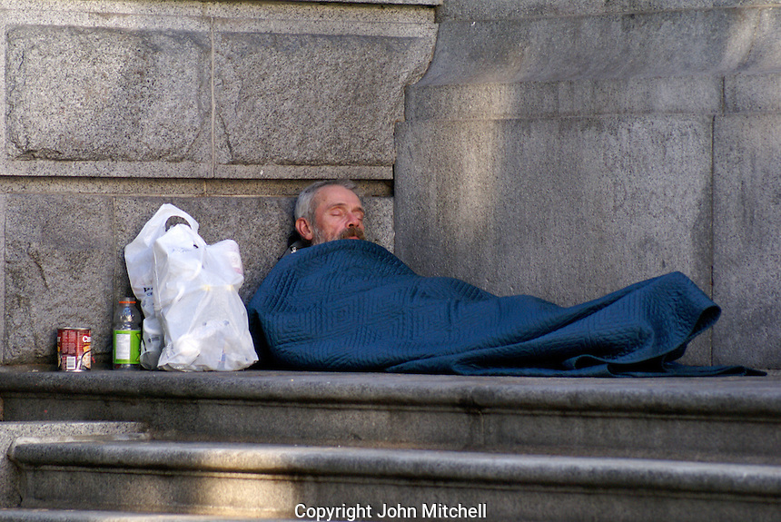Homeless man sleeping on steps in downtown Vancouver, British Columbia, Canada
