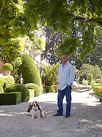 Fawaz Gruosi with two Basset hounds in the gardens surrounding his villa