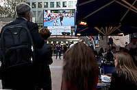 30 JUN 2011 - LONDON, GBR - Spectators watch events unfold on a TV screen during the GE Canary Wharf Triathlon .(PHOTO (C) NIGEL FARROW)