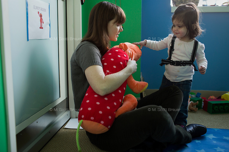 Melissa Kline (left), graduate student in the Department of Brain and Cognitive Sciences, works with Madeline Wilson in the Early Childhood Cognition Lab at MIT in Cambridge, Massachusetts, USA. Kline's research is looking at language usage and development in young children.  The backpack worn by Madeline holds a microphone that records her speech during the experiment.