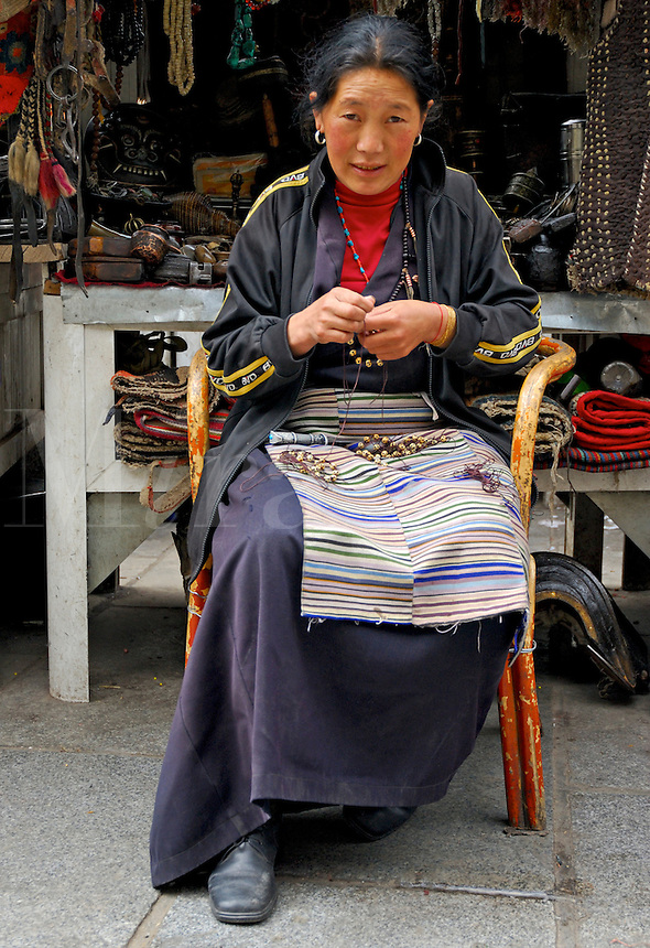 Tibetan handicrafter making yak bone bracelets for sale at her market stall on the Barkhor pilgrim circuit, Lhasa, Tibet.