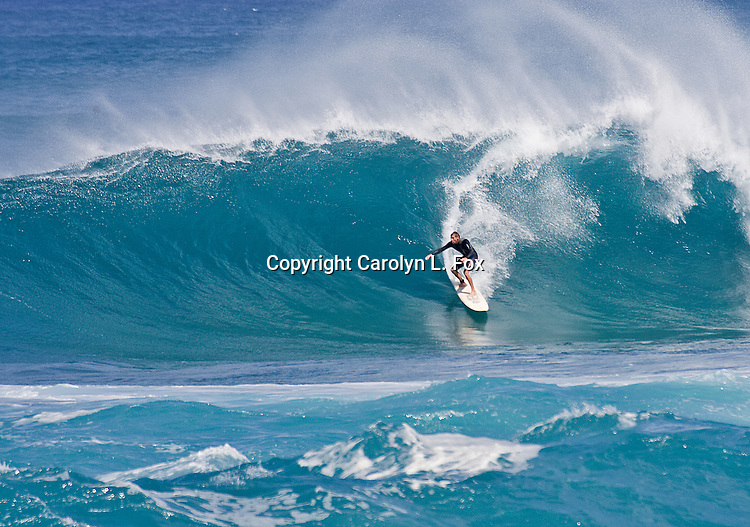 A man is surfing the big waves in Hawaii.