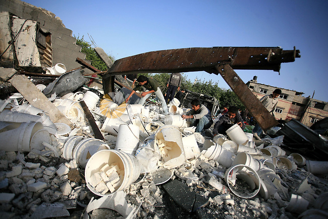 Palestinians inspect the damage at a cheese factory which was targeted by an overnight Israeli airstrike in Gaza City on April 2, 2010. Israel threatened a widescale military operation against the Gaza Strip after a string of air strikes which injured three Palestinian children following rocket attacks from the enclave. Three Palestinian children aged two, four and 11 were hit by flying glass in one of the six overnight raids, said the head of the Palestinian emergency services in Gaza.. Photo by Mohammed Othman