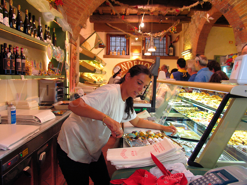 Greve in Chianti, Italy, woman working behind the counter in bakery delicatessen packaging cookies for a customer