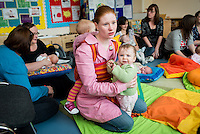 "Young mothers chatting while in the backgound a breastfeeding consultant gives advice to a mother who is breastfeeding her baby at a drop-in breastfeeding support centre.<br /> <br /> Image from the ""We Do It In Public"" documentary photography project collection: <br />  www.breastfeedinginpublic.co.uk<br /> <br /> Dorset, England, UK<br /> 17/04/2013"