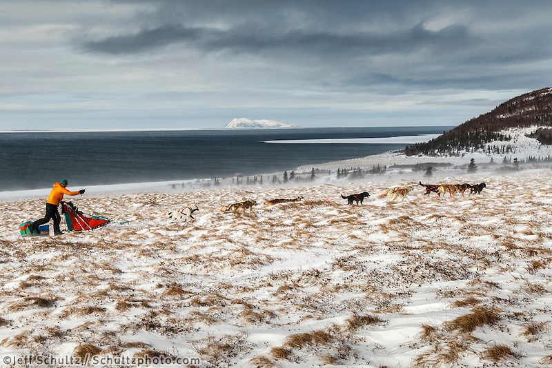Kelly Maixner runs on the trail through tussocks in 30 mph wind several miles after leaving the Unalakleet checkpoint with the Bering Sea and Besboro Island in the background on Monday March 16, 2015 during Iditarod 2015.    <br /> <br /> (C) Jeff Schultz/SchultzPhoto.com - ALL RIGHTS RESERVED<br />  DUPLICATION  PROHIBITED  WITHOUT  PERMISSION