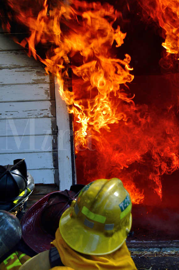 Firefighter trainees watch as flames billow out of a doorway of a house during a house training burn for the Goldridge Fire Academy Training Class.