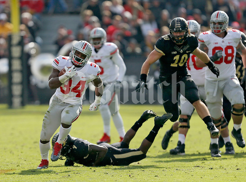 Ohio State Buckeyes running back Carlos Hyde (34) gets away from Purdue Boilermakers defensive back Anthony Brown (9) and Purdue Boilermakers linebacker Sean Robinson (10) during the first half of the NCAA football game at Ross-Ade Stadium in West Lafayette, IN on Saturday, November 2, 2013. (Columbus Dispatch photo by Jonathan Quilter)