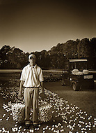A young boy working at a golf course holds baskets full of golf balls while even more lie on the ground around him