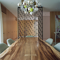A metal screen by Malcolm Hill separates the dining room from the rest of the house and a chandelier by Susan Etkin hangs over the bespoke dining table