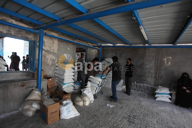 Palestinians wait to receive food supplies from a distribution centre of the United Nations Relief and Works Agency (UNRWA) in Gaza City on August 11, 2014. An Israeli delegation arrived in Cairo for indirect negotiations with Palestinians on a durable truce in Gaza, Egypt and Israeli officials said. Photo by Ashraf Amra