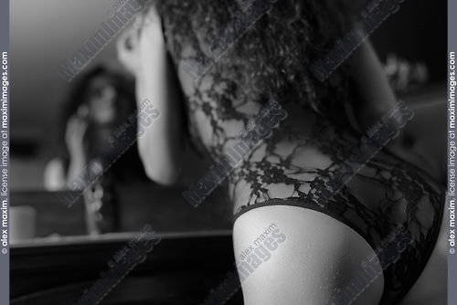 Artistic sensual black and white closeup of a young woman in sexy black lacy underwear leaning onto a dresser towards the mirror applying lipstick. French retro style boudoir.