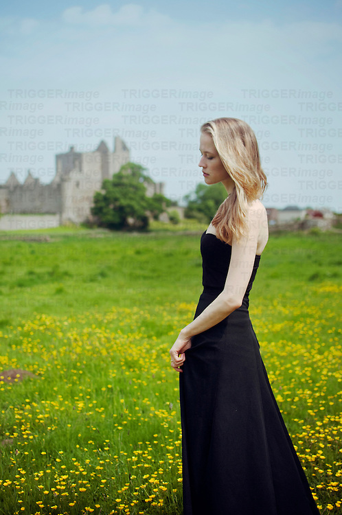 Young woman in black dress walking towards distant castle through field of flowers