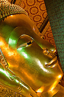 A golden statue of the Buddha sits smiling, or smirking, in a Buddhist temple Bangkok, Thailand.
