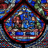 Haberdashery with shop keeper weighing out goods for a customer, from the donor window of the haberdashers from the Life of St Nicholas stained glass window, 13th century, in the North aisle of the nave of Chartres cathedral, Eure-et-Loir, France. St Nicholas, 270-343 AD, was born in Patara in Lycia (now Turkey) and was bishop of Myra. Chartres cathedral was built 1194-1250 and is a fine example of Gothic architecture. Most of its windows date from 1205-40 although a few earlier 12th century examples are also intact. It was declared a UNESCO World Heritage Site in 1979. Picture by Manuel Cohen