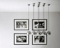 In a living room nine stainless steel pendant lights are suspended together in front of four framed black and white photographs