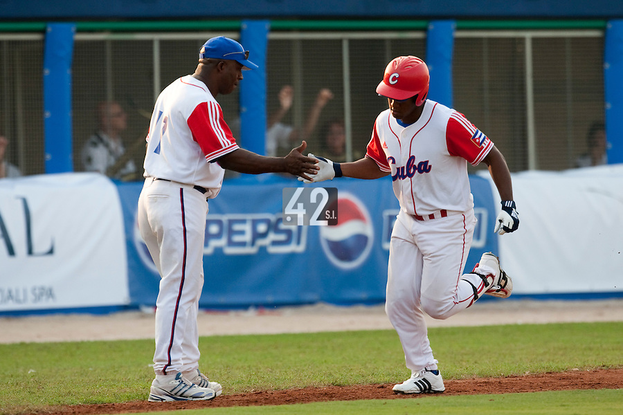 27 September 2009: Alfredo Despaigne of Cuba is congratulated by third base coach Luis Jova as he runs the bases after a record 11th home run to cut the margin to 10-6 in the eighth inning during the 2009 Baseball World Cup gold medal game won 10-5 by Team USA over Cuba, in Nettuno, Italy.