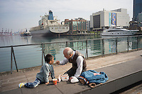 An old man feeds his grandson at the Keelung Port in Taiwan, 2015. Keelung is a major port city situated in the northeastern part of Taiwan. The city is Taiwan's second largest seaport.
